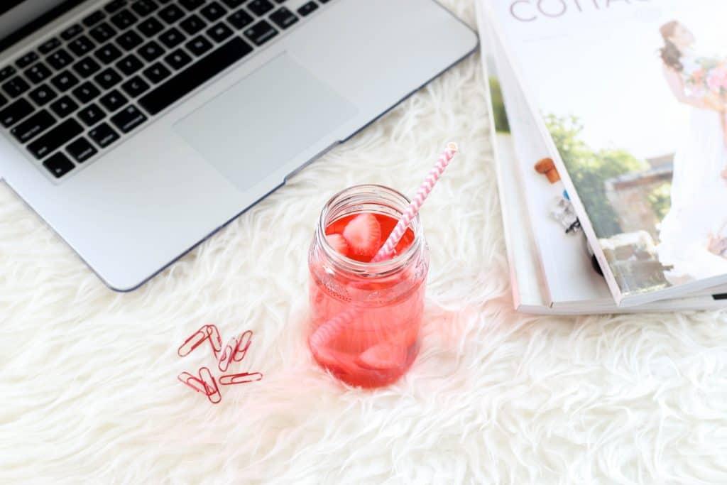 working on laptop while drinking Plexus pink drink