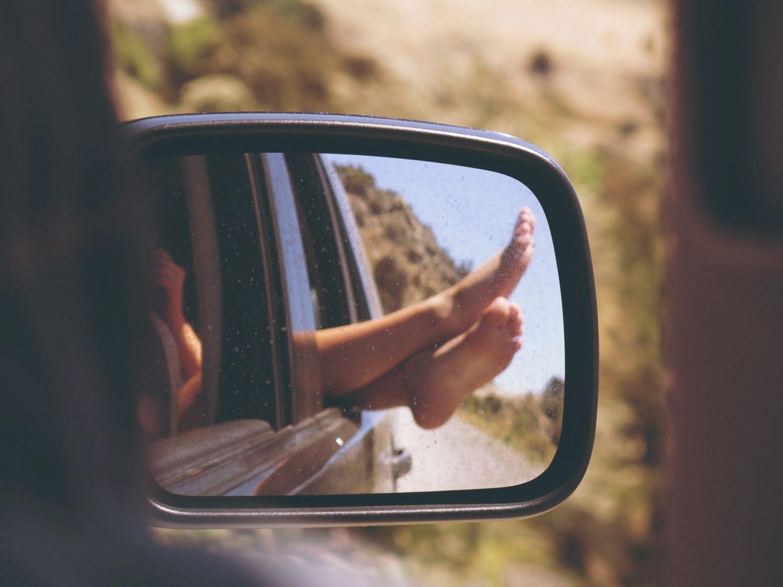 woman's feet in rear view mirror